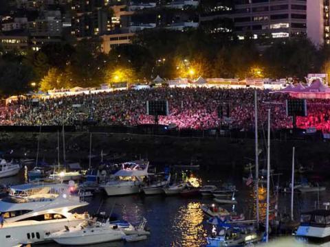 워터프런트 블루스 페스티벌의 네온 조명 장식 앞에 모여든 군중